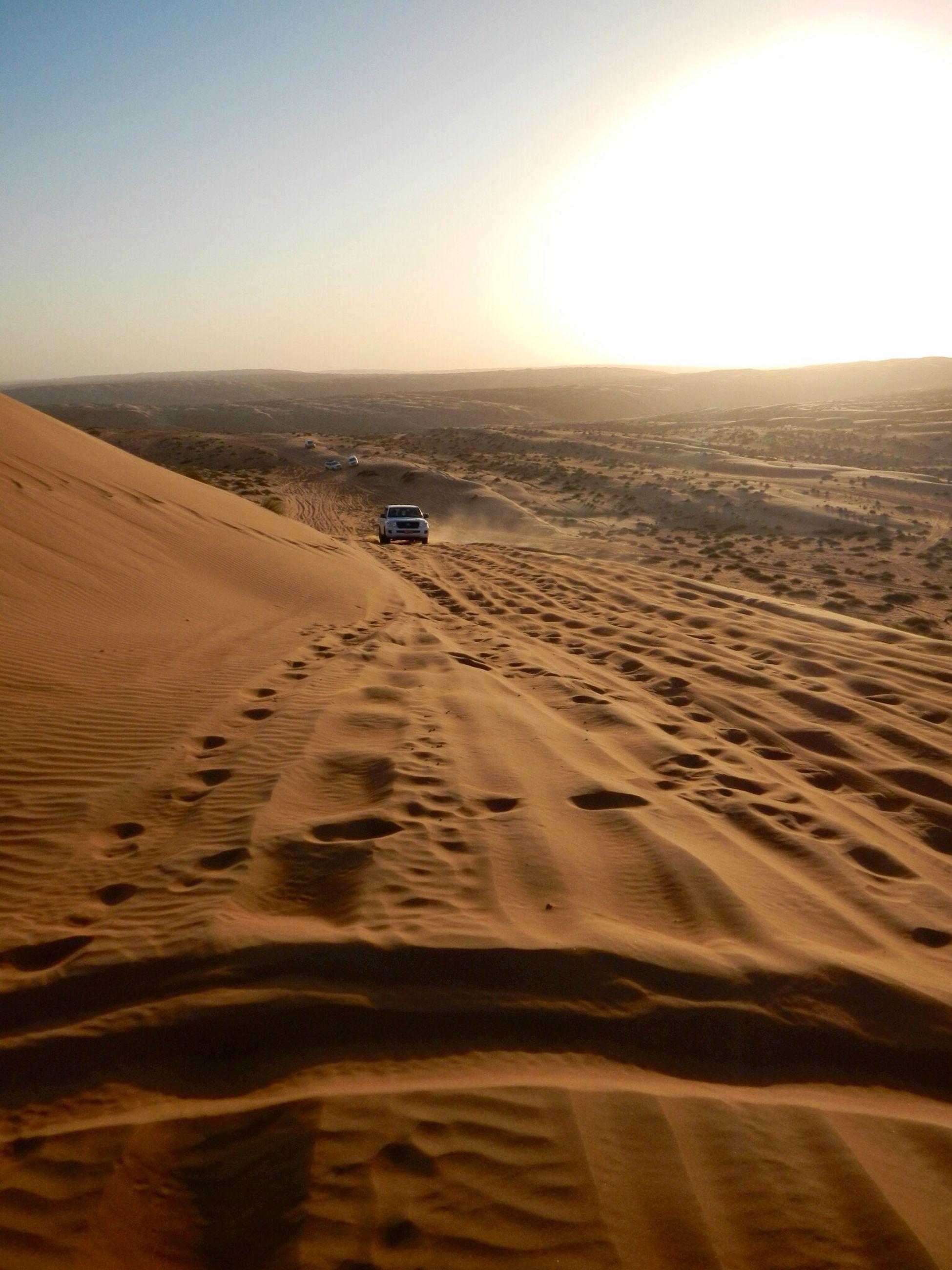 sand, sand dune, tranquil scene, tranquility, beach, desert, scenics, landscape, beauty in nature, nature, footprint, sunlight, arid climate, clear sky, sunset, sky, sun, horizon over land, idyllic, sea