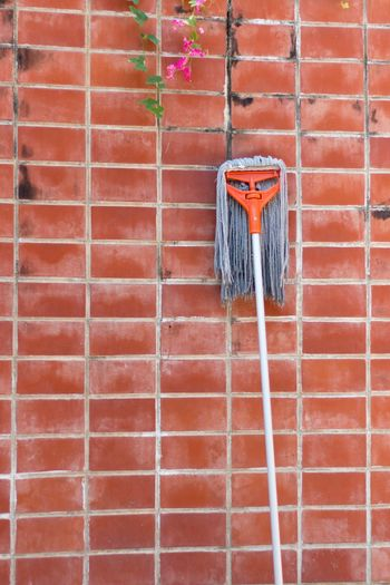 Close-up of mop leaning on brick wall