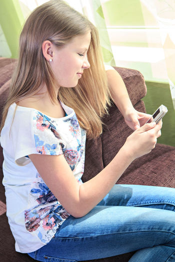 Side view of young woman using smart phone while sitting on sofa at home