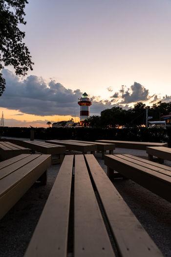 Railroad station platform against sky during sunset