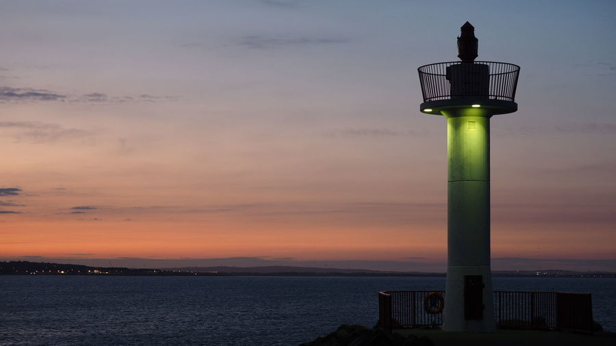 Scenic view of lighthouse by sea against sky during sunset