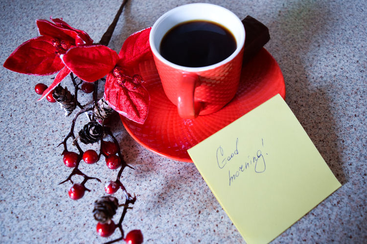 Close-Up Of Black Coffee With Red Berries And Note On Table