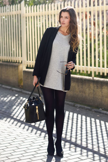 Thoughtful Young Woman Holding Handbag While Standing On Footpath