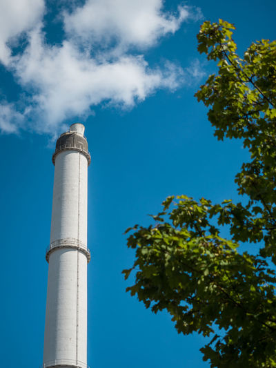 Low angle view of chimney and tree against sky