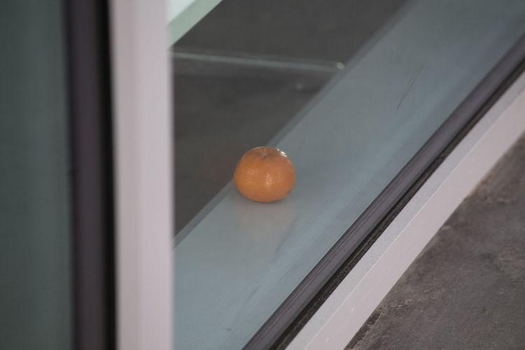 Close-up of orange fruit on window
