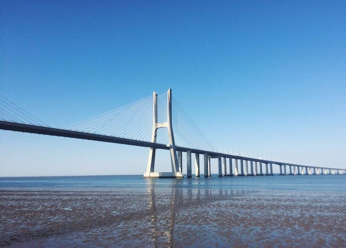 April 25th bridge over tagus river against clear blue sky