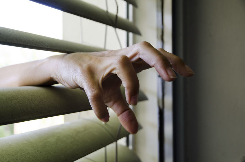 Cropped Hand Of Woman Amidst Window Blinds
