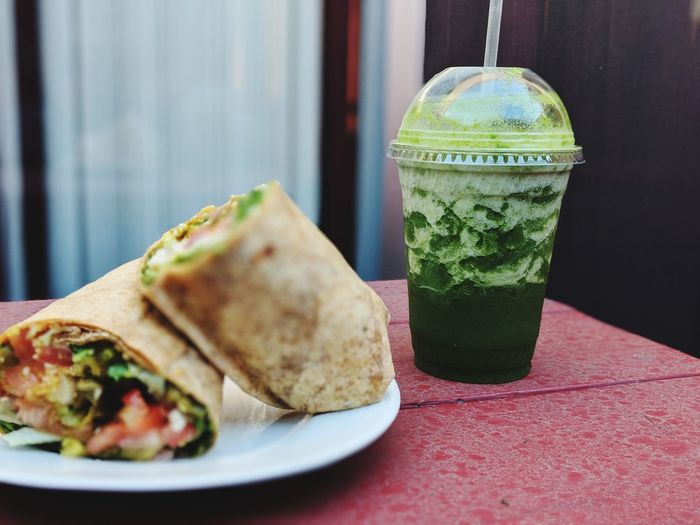 Close-Up Of Wrap Sandwich And Drink On Table