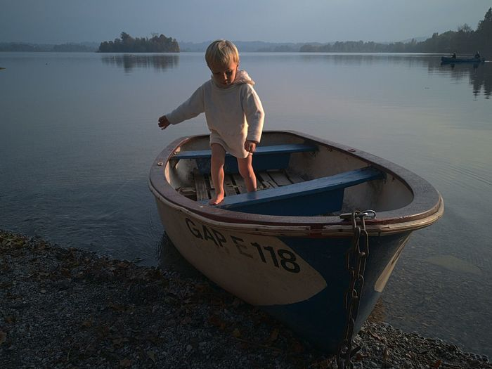 Boy standing on boat in lake