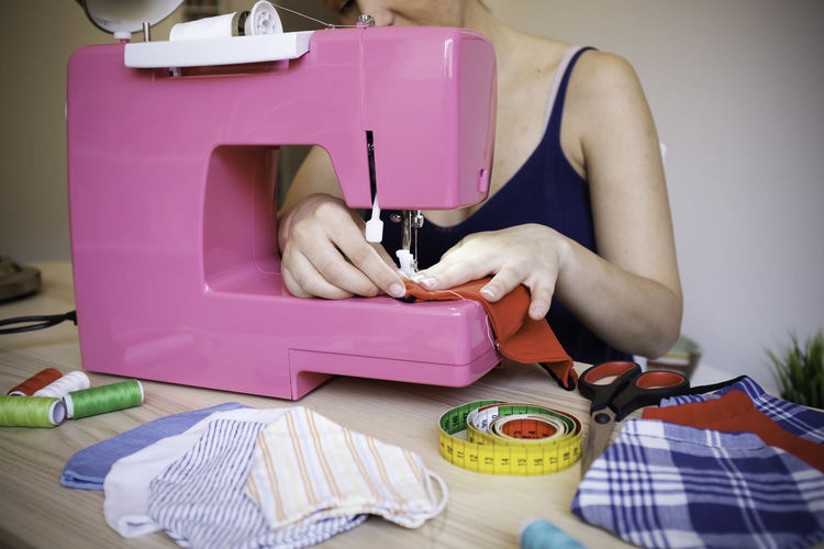 Midsection of woman stitching fabric
