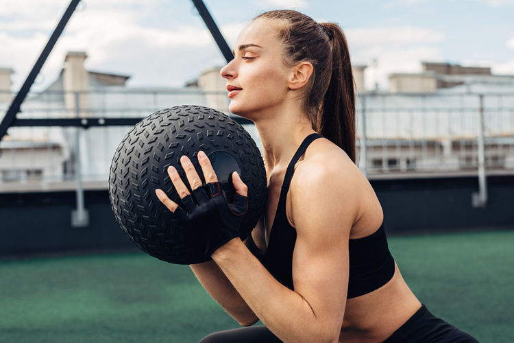 Young woman exercising with ball on terrace