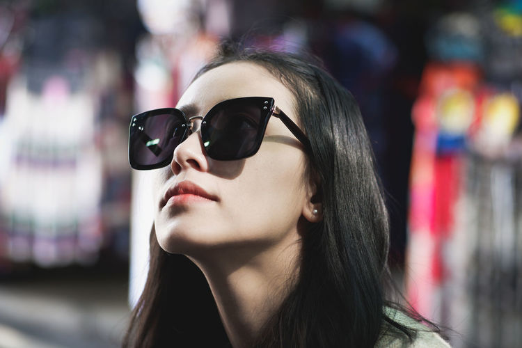 Close-up of woman wearing sunglasses at night