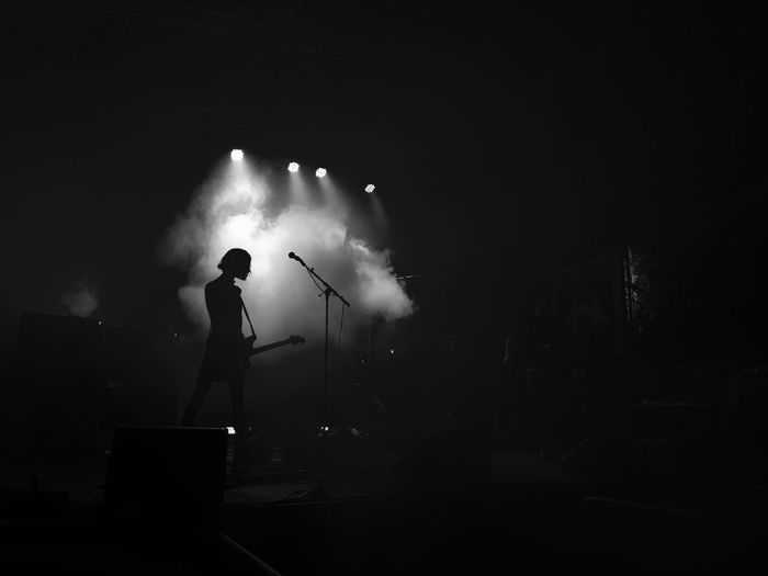 Rear view of silhouette person playing guitar during concert