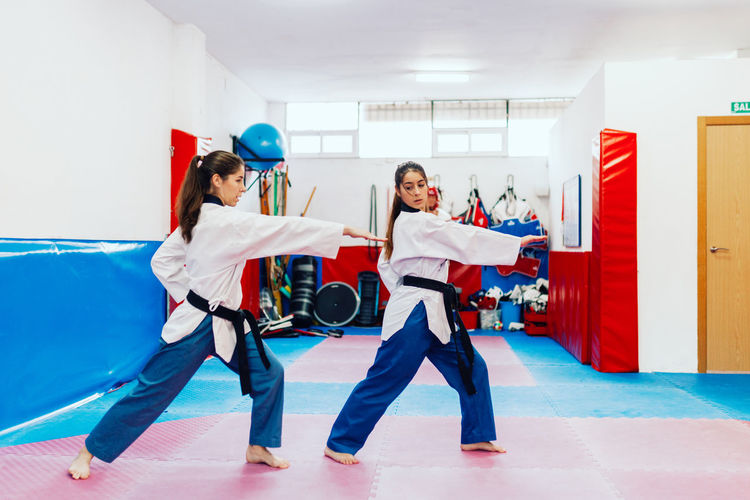 Full length of young woman with instructor practicing martial arts