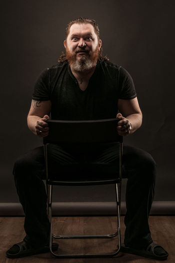 Adult Beard Black Background Casual Clothing Chair Facial Hair Front View Full Length Indoors  Looking At Camera Males  Mature Adult Mature Men Men Mid Adult Mid Adult Men One Person Portrait Real People Sitting