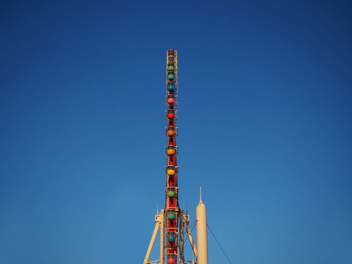 Side view of a ferris wheel and blue sky.