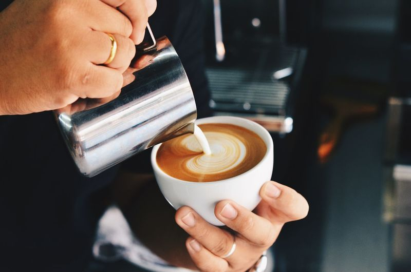 Barista pouring milk in coffee cup for making latte art. Barista Cafe Cappuccino Close-up Coffee - Drink Coffee Cup Day Drink Food And Drink Freshness Froth Art Frothy Drink Holding Human Body Part Human Hand Indoors  Latte Making Milk Mocha One Person People Real People Refreshment