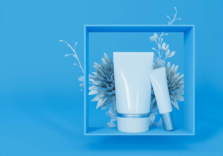 Flower vase on table against blue background