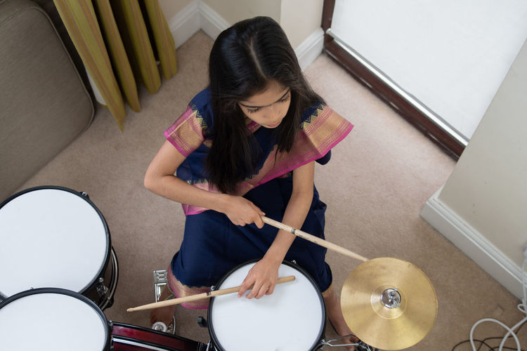 High angle view of girl in sari playing drum