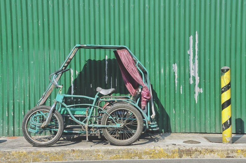 Tricycle Parked By Corrugated Iron