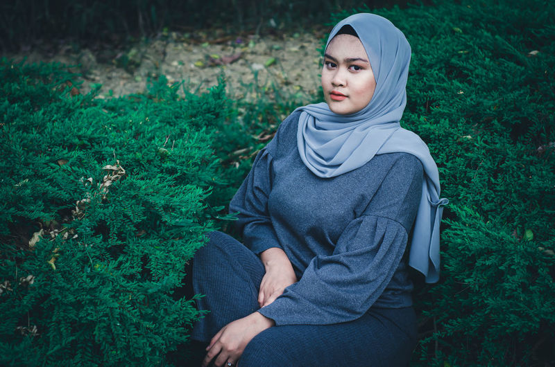 Portrait Of Young Woman In Hijab Sitting Amidst Plants On Field