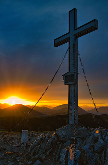 Cross on snow covered mountain against sky during sunset