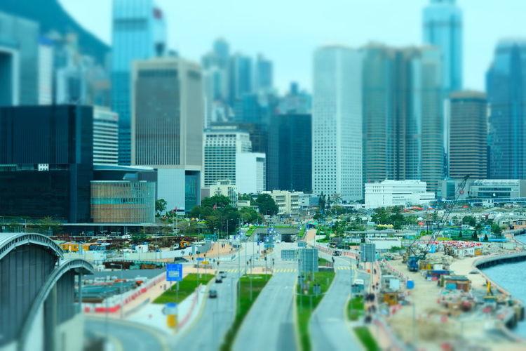 Tilt-shift image of modern buildings in city against sky