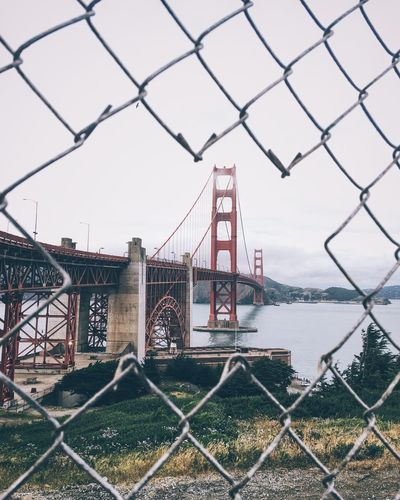Architecture Bridge - Man Made Structure Built Structure Chainlink Chainlink Fence City Connection Day Metal No People Outdoors Protection Safety Sky Suspension Bridge Transportation Travel Destinations Water