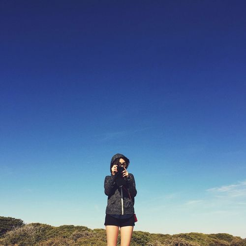 Portrait of young woman photographing against blue sky