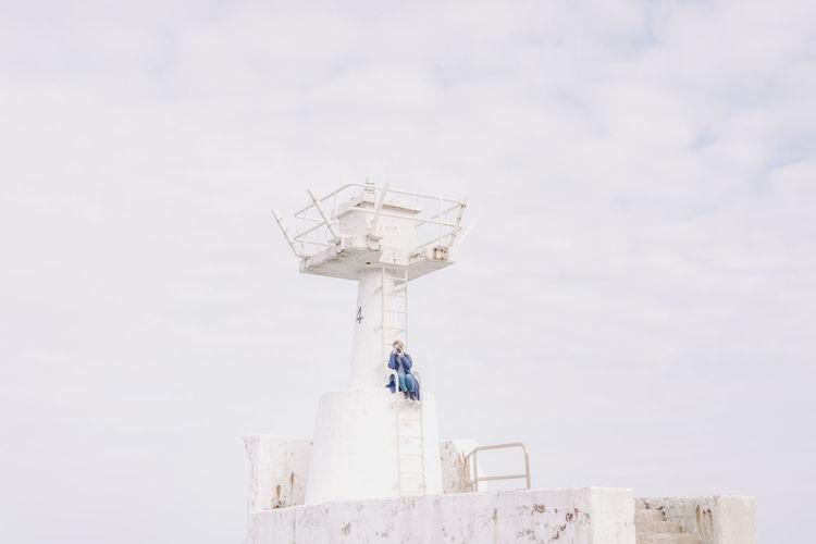 Low angle view of woman photographing while sitting on lookout tower against sky