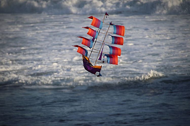 Colorful boat kite flying against sea