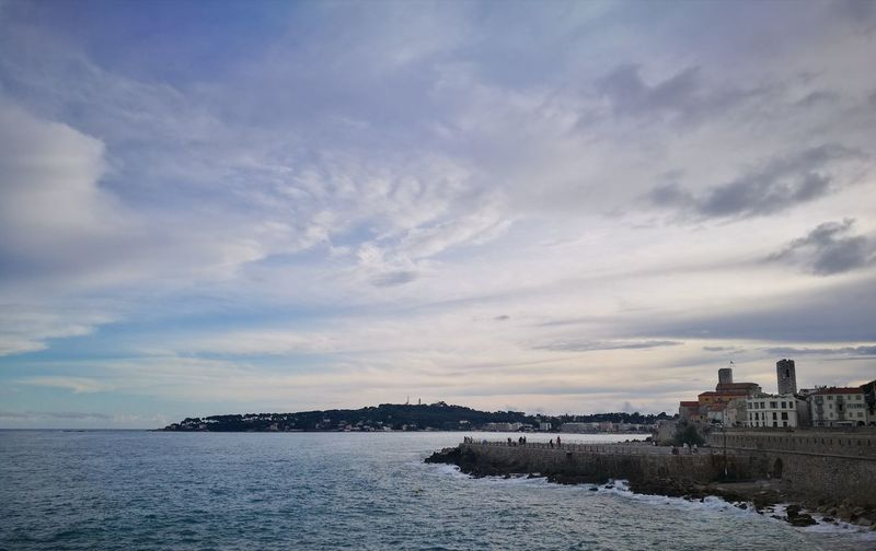 Scenic view of sea by buildings against sky