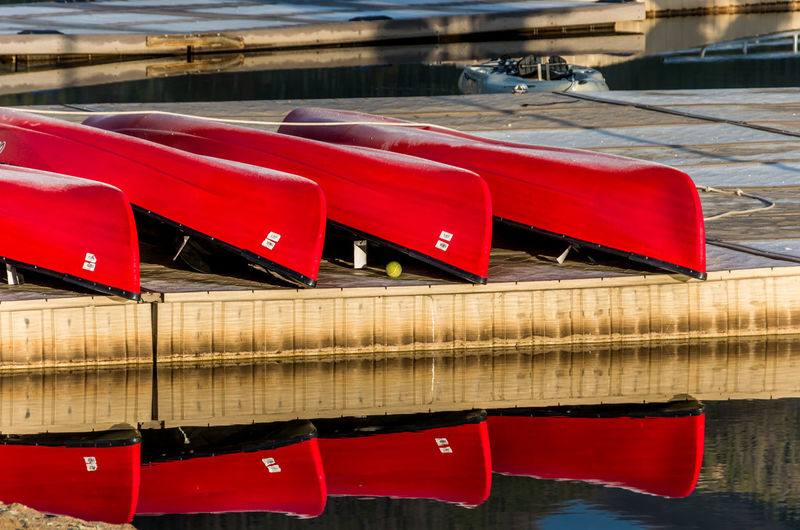 Red deck chairs by river
