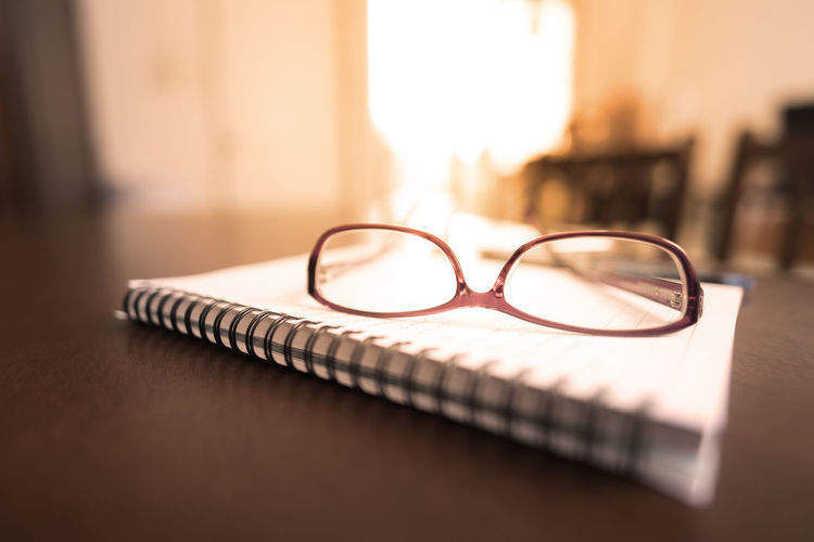 Close-up of eyeglasses and book on table at home
