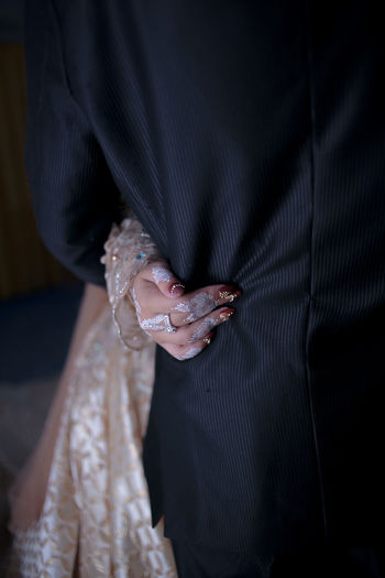 Midsection of bride holding groom at home