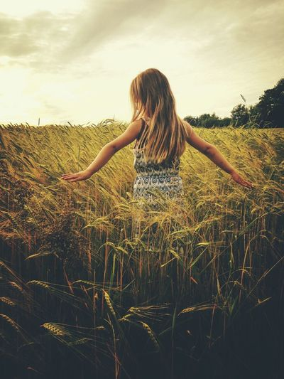 Young girl playing in a field. Cute Kids Being Kids Kid Sweet Girl Outdoors Outside Clouds Landscape Landscape_Collection Children Quiet Moments Quiet Emotions Family Solitude Nostalgia Nostalgic  Mysterious Hair Hairstyle Innocence Youth Of Today Youth