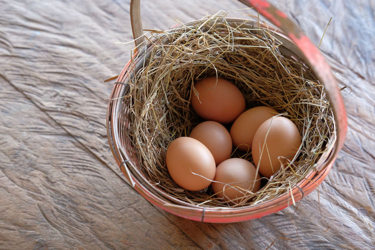 chicken eggs in basket Chicken Animal Egg Basket Brown Chicken Eggs Close-up Day Egg Food Food And Drink Fragility Freshness Healthy Eating High Angle View Indoors  No People Straw Table Wooden