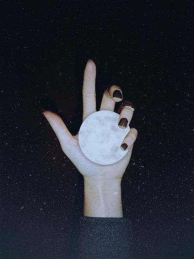 Cropped Image Of Woman Holding Sphere Against Black Background