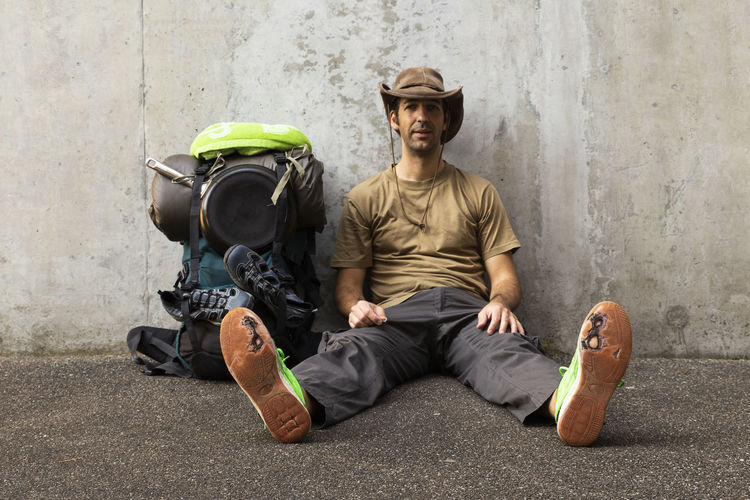 Portrait of man sitting with backpack on footpath against wall