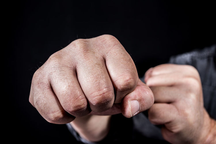 an aggressive punch Aggression  Mercilessly Adult Assault Attack Black Background Black Color Body Part Brutalism Close-up Contemplation Finger Fist Hand Human Arm Human Body Part Human Finger Human Hand Indoors  Limb Men People Punch Studio Shot Unmerciful