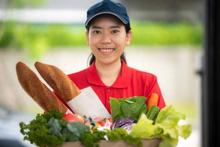 Portrait of smiling young woman holding food