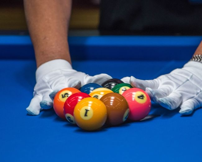 Midsection of man arranging pool balls on table