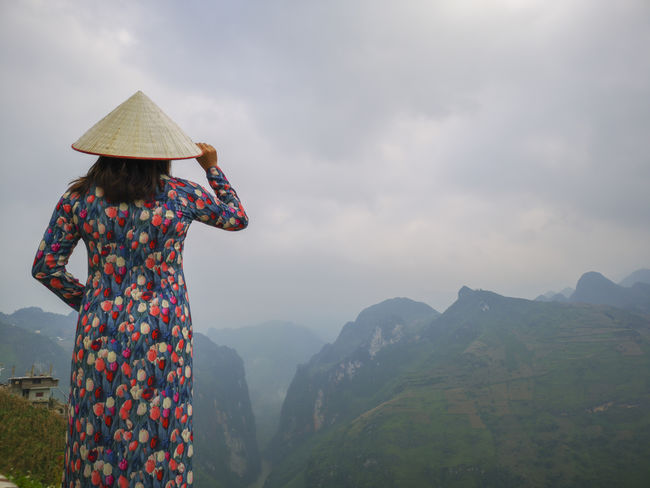Young Vietnamese women facing and pose for camera with stunning view of the Nho Que river surrounded by mountains from the Ma Pi Leng pass in northern Vietnam Mountain Cloudy Green Color Meo Vac Vietnam Vietnamese Adult Ao Dai Beauty In Nature Clothing Cloud - Sky Day Hat Landscape Leisure Activity Lifestyles Looking At View Mountain Mountain Range Nature Non-urban Scene One Person Outdoors People Pose Real People Rear View Scenics - Nature Sky Standing Sunrise Traditional Dress Tranquil Scene Valley Women