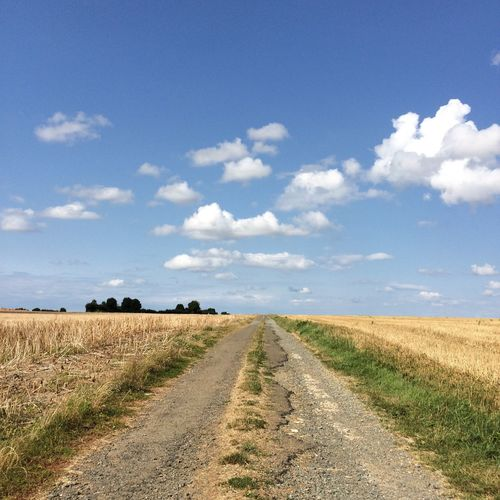 Country road on agricultural field against cloudy sky