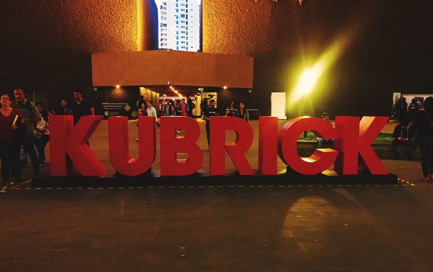 Kubrick Illuminated Text Night Communication Large Group Of People Real People Built Structure Lifestyles Architecture Neon Outdoors People