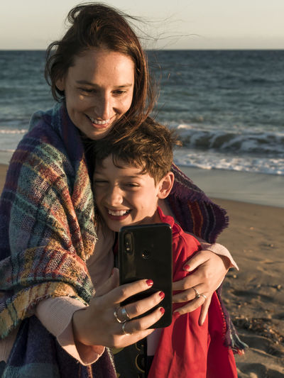 Mother and son doing selfie while standing at beach