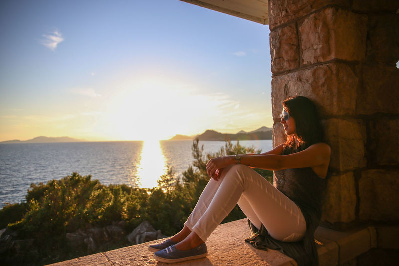 Smiling woman sitting on retaining wall by sea against sky during sunset