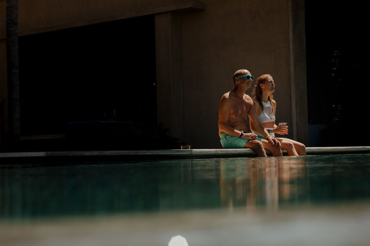 Couple sitting at pool side
