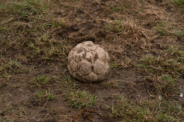 Traces Of Neglect And Dissolution Ball Broken Cloe Up Layered Rocks Decay Field Grass High Angle View Leather Misplaced No People Outdoors Soccer
