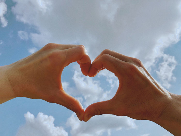 Cropped image of hand holding heart shape against sky